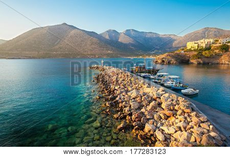 Bali Island Crete Greece - June 24 2016: Beautiful morning scenery scenery with mountains Mediterranean sea and pier with boats of local fishermen and the big old wooden ship for walking tourists in the sea near village Bali that is located on the coast.