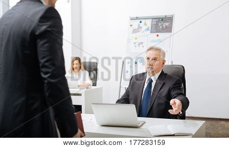 The process of dismissal. Concentrated confident aged employer sitting in the office while working and having conversation with employee