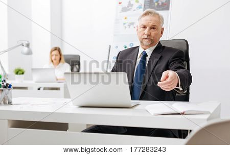 Ready for serious conversation. Arrogant confident aged employer sitting in the office while working and getting ready for conversation with employee