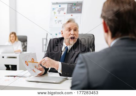 Full of negative. Fierce furious angry employer sitting in the office and having conversation with employee while expressing anger and yelling