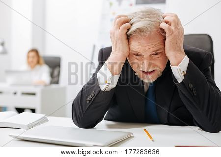Negation of defeat. Bearded furious annoyed employer sitting in the office and touching his head while expressing anger