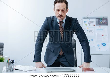 Never put out of temper me . Powerful angry fierce businessman standing in the office and leaning on the table while expressing anger