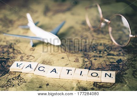 Vacation concept scrabble text and traveler equipment on vintage map