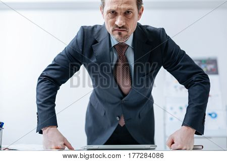 Full of hate. Athletic heated fierce businessman standing in the office and leaning on the table while expressing anger and doubling his fists