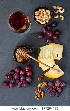 Wine, cheese, grapes, honey on stone background. Top view
