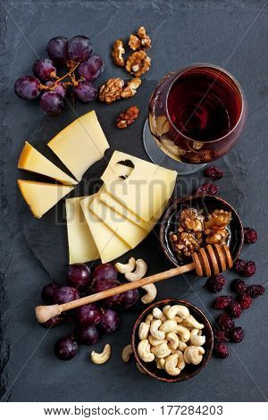 Cheese, grape and wine glass on dark stone background