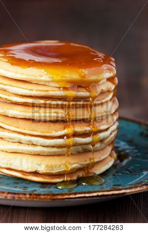 Pancakes with honey syrup on ceramic plate. Traditional crepes for pancake week