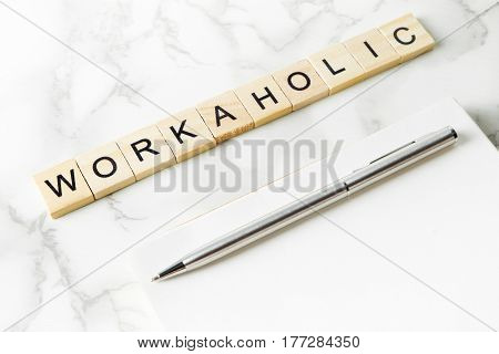Workaholic text on marble office table with copy space on notebook