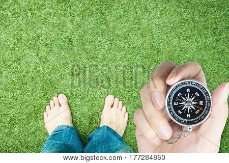 Explorer holding compass with bare feet ready to start walking with copy space