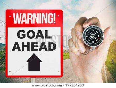 Warning sign goal ahead with hand holding compass for direction