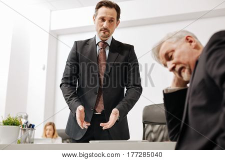 Lets find the way out. Puzzled unsure charismatic coworker working and discussing the project with colleague while exchanging opinions in the office