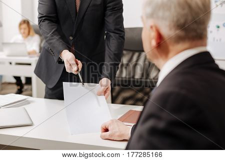 Important moment . Concentrated experienced aged employer sitting in the office and expressing concentration while signing the document and having conversation with employee