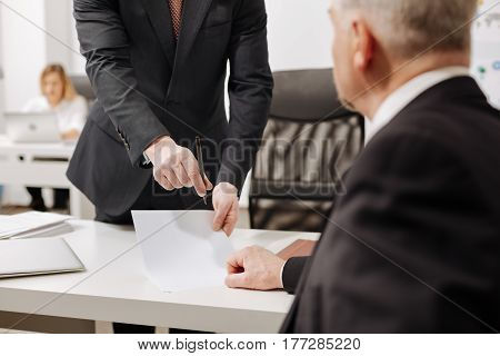 Business papers in my hands. Concentrated wise aged employer sitting in the office and expressing concentration while signing the document and having conversation with employee