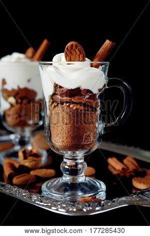 Sweet dessert with chocolate crumbles cocoa nuts whipped cream and cinnamon on silver tray