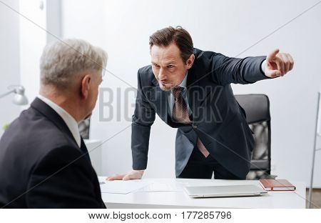 Putting you upon the shelf . Experienced furious angry boss working and expressing dissatisfaction while having conversation with employee and pointing out