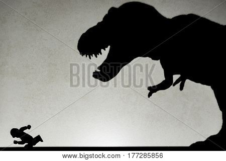 shadow of tyrannosaurus chasing human on wall no logo or trademark
