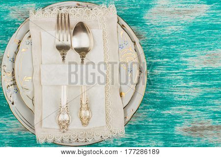 Tableware and silverware on the light blue background top view