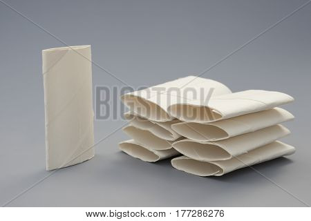 smashed toilet rolls stack up on grey background