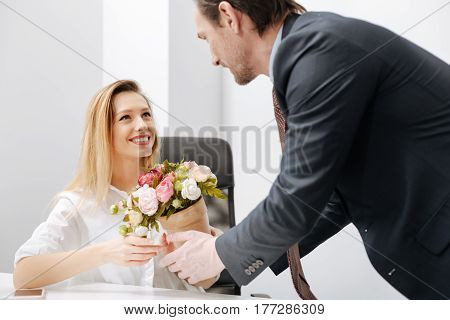 Little surprise for you. Charismatic charming delighted employer holding the bouquet while standing near the employee and having conversation