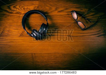 headphones on a wooden table with accessory such as phone, glasses. Concept of music. Retro design