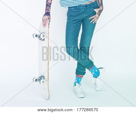 Woman standing and posing for picture with skateboard