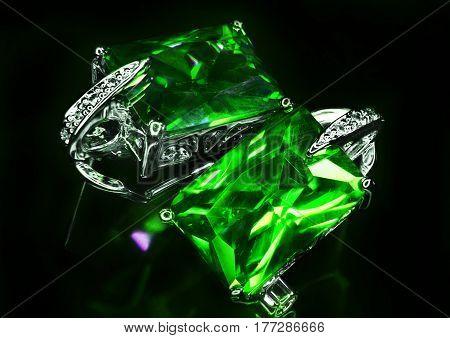 Jewel earrings with green stones and diamonds closeup photo.