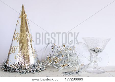 Styled party scene with silver party hat, streamers, and cocktail glasses with silver stars. Open space for copy.