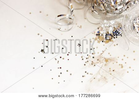 Elegant party supplies with silver streamers and stars surrounding elegant cocktail glasses. Open space for copy.