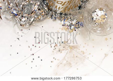 Fun and elegant silver party scene with streamers, party hat, cocktail glasses, and silver stars. White marble space for copy.