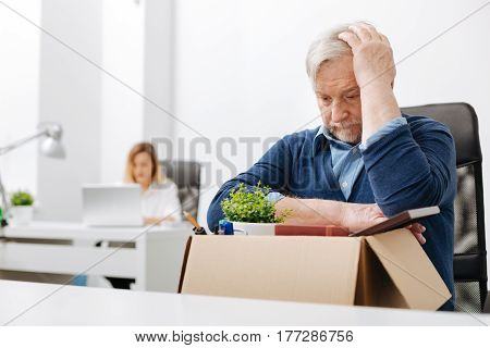 The worse day ever. Thoughtful depressed aged office worker sitting in the office and gathering his belongings while holding the box and expressing despair