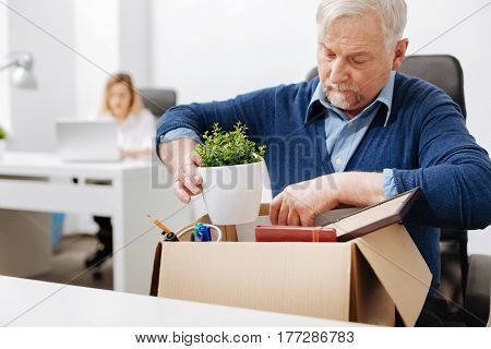 Challenge of my life . Involved unnerved aged office manager sitting in the office and gathering his belongings while holding the box and expressing despair