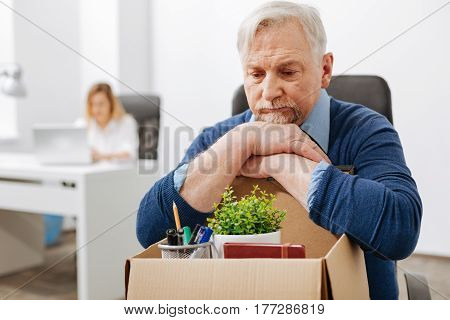 Jobless from this minute . Concentrated sad aged employee sitting in the office and gathering his belongings while holding the box and expressing melancholy
