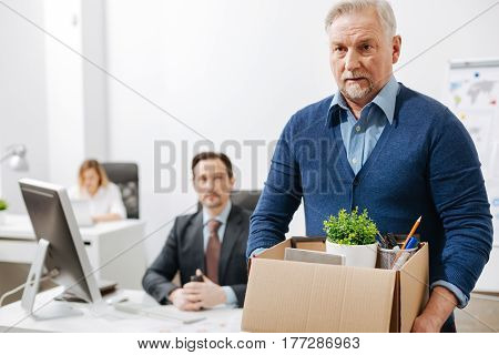 Quitting my responsibilities here. Fired involved aging employee standing and holding the box with his belongings while leaving the office