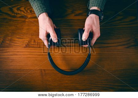 Man hand keep headphones on a wooden table with accessory such as phone, glasses. Concept of music