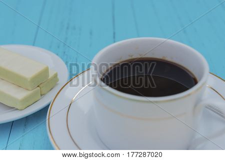 side view cup of coffee and white chocolate wafer on a blue ackground