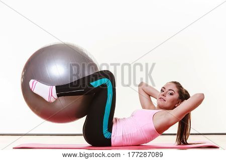 Sport gym fitness people concept. Beautiful lady with fit ball. Woman has sporty outfit leggins tshirt.