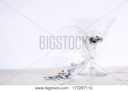 Elegant etched cocktail glasses spilling with silver metallic stars framing open white space for copy