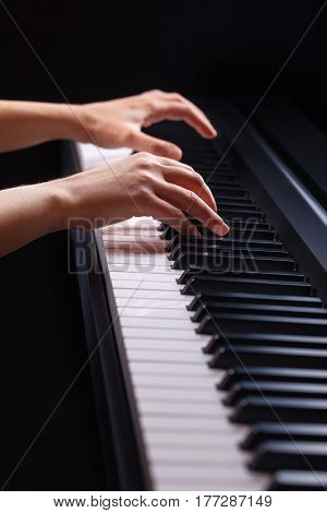 Close-up of a female hands playing piano on a black background