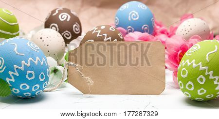 Painted easter eggs and branches of spring sakura closeup on a light blue background with space for congratulation