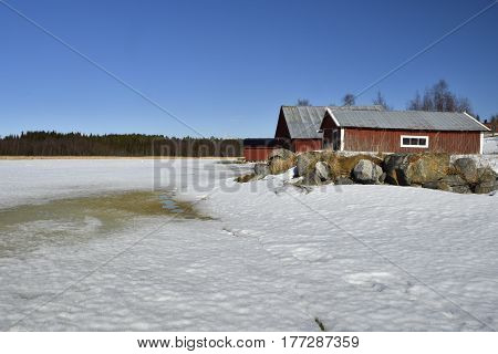 Melting sea ice in spring sun and rocks and three red boathouse against a blue skypicture from the North of Sweden.