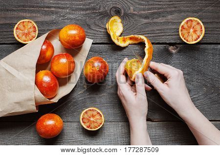 Female hands cut juicy orange, aged wooden table