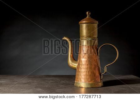 an old copper coffeepot on a black background