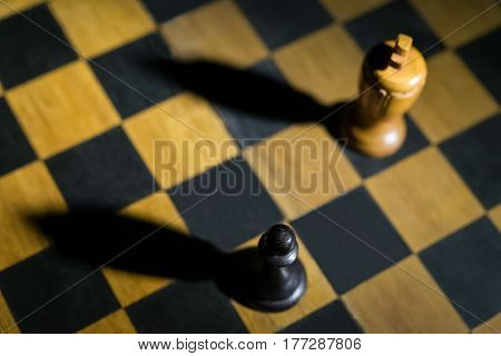 chess pawn casting a king piece shadow on chessboard concept of strength and aspirations