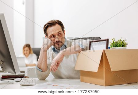 Thinking about disappointed plans. Fired perplexed upset manager sitting and holding the box with his belongings while expressing sadness