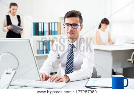 Young handsome businessman smiling at camera when using computer in the office