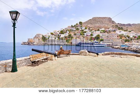 HYDRA ISLAND GREECE, MAY 27 2016: woman tourist looks at the landscape of Hydra island Greece. Editorial use.