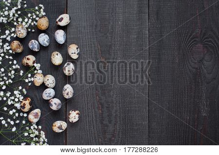 Quail Eggs And Flowers On The Wooden Brown Table