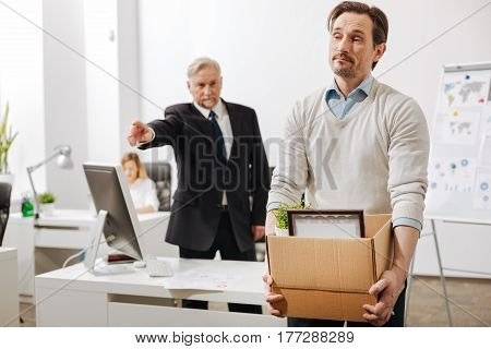 Surviving difficulties at work. Confident serious angry employer standing and pointing out while firing the employee from the job