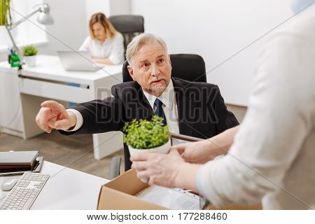 Telling goodbye to some employees. Aged serious confident employer sitting and pointing out while firing the employee from the company