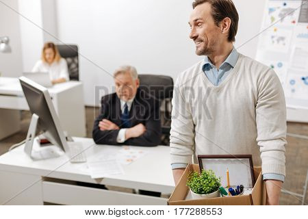 New step in my life. Fired delighted positive employee standing and carrying the box with his personal stuff while expressing happiness and leaving the company